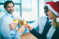 Business people with champagne celebrating Christmas at office party - stock photo