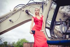 The blonde in a red dress on the excavator, beauty fashion, autumn - stock photo