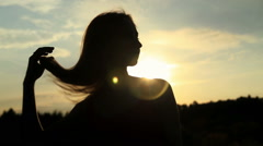 A silhouette of a woman  on a sunset touching her hair Stock Footage