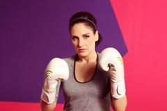Portrait of a female boxer with gloves - stock photo