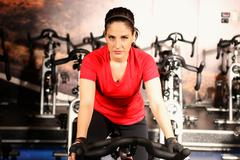 Young athletic women pedaling on a indoor bicycles gym - stock photo