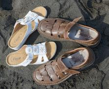 Two pair of men's and women's shoes nearby on sand. - stock photo