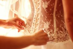 Stock Photo of Bride getting ready for wedding helped with the corset