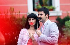 Joyful couple having fun with moustache in the park Stock Photos