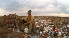 man homeless beggar sitting in a landfill with a hat asks for money food waste - stock footage