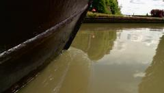 Low Shot of a Narrowboat Steering Down a River Stock Footage