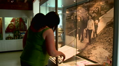 People Viewing Old Documents Inside Glass Case Stock Footage