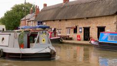 A White Narrowboat Steers Past a Riverside Pub Stock Footage