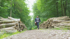 4K Happy hipster businessman running through the woods with briefcase - stock footage