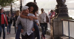 A happy youjng man giving his girlfriend a piggyback ride outside in the street. Stock Footage