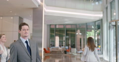 Portrait of Businessman at work in busy office lobby Stock Footage