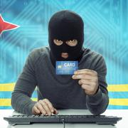 Dark-skinned hacker with flag on background holding credit card - Aruba - stock photo