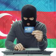 Dark-skinned hacker with flag on background holding credit card - Azerbaijan - stock photo