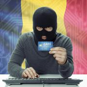 Dark-skinned hacker with flag on background holding credit card - Chad - stock photo