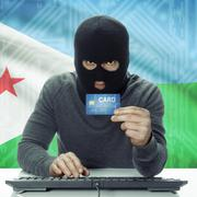 Dark-skinned hacker with flag on background holding credit card - Djibouti - stock photo