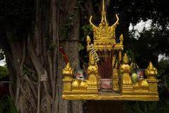 Horizontal close up of a gold spirit house with large tree in the background, Stock Photos