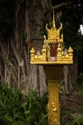 Medium close up of a gold spirit house with large tree shimmering in the dusk Stock Photos
