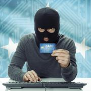 Dark-skinned hacker with flag on background holding credit card - Micronesia Stock Photos
