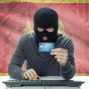 Dark-skinned hacker with flag on background holding credit card - Montenegro Stock Photos