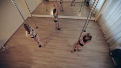 Girls training pole dance in a studio - stock footage