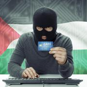 Dark-skinned hacker with flag on background holding credit card - Palestine - stock photo