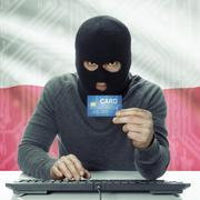 Dark-skinned hacker with flag on background holding credit card - Poland - stock photo
