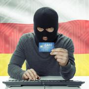 Dark-skinned hacker with flag on background holding credit card - South Osset - stock photo