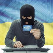 Dark-skinned hacker with flag on background holding credit card - Ukraine - stock photo