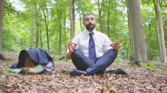 4K Hipster businessman sitting alone in the woods & meditating.  - stock footage