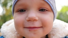 Little kid boy cute face closeup looking at camera without one front tooth Stock Footage