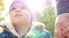 LIttle kid boy face closeup holding hands with father in autumn park Stock Footage