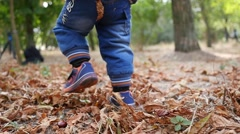Little kid legs running on autumn yellow fallen leaves in park - low legs camera Stock Footage