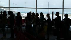 Black passenger silhouettes against apron window, international airport Stock Footage