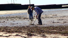 A Man Searches for Treasure on the Beach with a Metal Detector Stock Footage