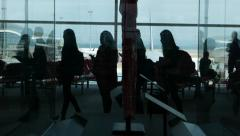 Airport passengers black silhouettes walk stand queue against wall window Stock Footage