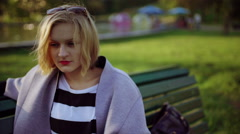 Girl sitting in the park and looking melancholic Stock Footage