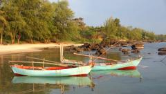 Small bay between rocks with two blue green small fishing boat ship Stock Footage
