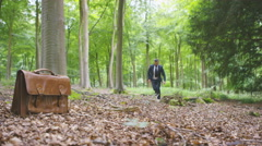 4K Quirky hipster businessman running through the woods Stock Footage