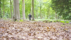 4K Quirky hipster businessman running through the woods - stock footage