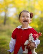 A cute little happy girl holding a teddy bear in the  on a sunny autumn day Stock Photos