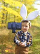 Funny little kid boy with Easter bunny ears taking a selfie with a selfie sti - stock photo