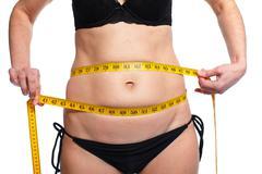 Woman measuring fat abdomen. - stock photo
