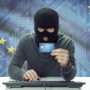 Stock Photo of Dark-skinned hacker with credit card and USA states flag on background - Alas