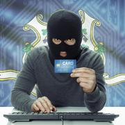 Stock Photo of Dark-skinned hacker with credit card and USA states flag on background - Conn