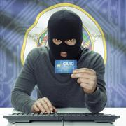 Dark-skinned hacker with credit card and USA states flag on background - Minn - stock photo
