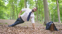 4K Hipster businessman doing yoga in the woods & making phone call  Stock Footage