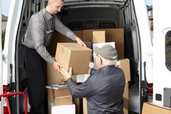Group of delivery men near shipping truck. - stock photo