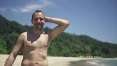 Portrait of happy, handsome man walking on beach, slow motion 240fps Stock Footage