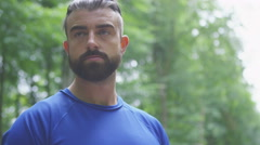 4K Young man in fitness clothing using wireless device in the woods Stock Footage