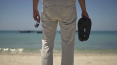 Stock Video Footage of Man with sandals and sunglasses standing on beach, slow motion 240fps
